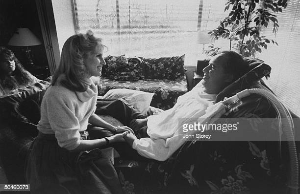 Former high school football coach/ALS victim Charlie Wedemeyer reclining on couch wearing respirator as wife Lucy holds his hand daughter Carri sits...