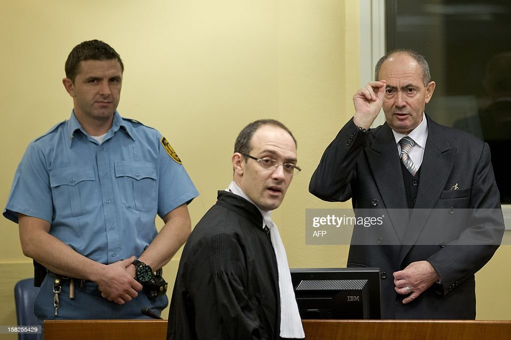 Former high-ranking Bosnian Serb general Zdravko Tolimir,(R), crosses himself as waits for the the Yugoslav war crimes tribunal to deliver its judgement and sentence for genocide charges for his role in the 1995 Srebrenica massacre in The Hague on December 12, 2012. German judge Christoph Flugge is to read his judgement and sentencing before the International Criminal Tribunal for the former Yugoslavia shortly after the hearing starts at 3:00 pm (1400 GMT) before the Hague-based tribunal with the Prosecutors asking a life sentence. AFP PHOTO / ANP / PETER DEJONG netherlands out