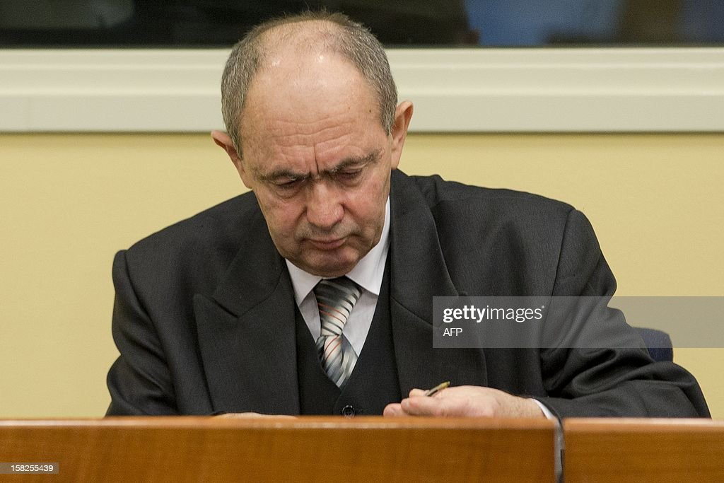 Former high-ranking Bosnian Serb general Zdravko Tolimir,(R), takes pen and paper out of his suitcase as he waits for the the Yugoslav war crimes tribunal to deliver its judgement and sentence for genocide charges for his role in the 1995 Srebrenica massacre in The Hague on December 12, 2012. German judge Christoph Flugge is to read his judgement and sentencing before the International Criminal Tribunal for the former Yugoslavia shortly after the hearing starts at 3:00 pm (1400 GMT) before the Hague-based tribunal with the Prosecutors asking a life sentence. AFP PHOTO / ANP / PETER DEJONG netherlands out