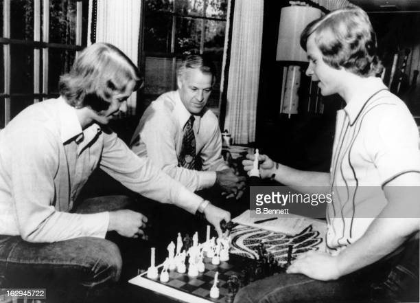 Former hockey player Gordie Howe watches his sons Marty and Mark play a game of chess as they relax at home on September 30 1973 in Bloomfield Hills...