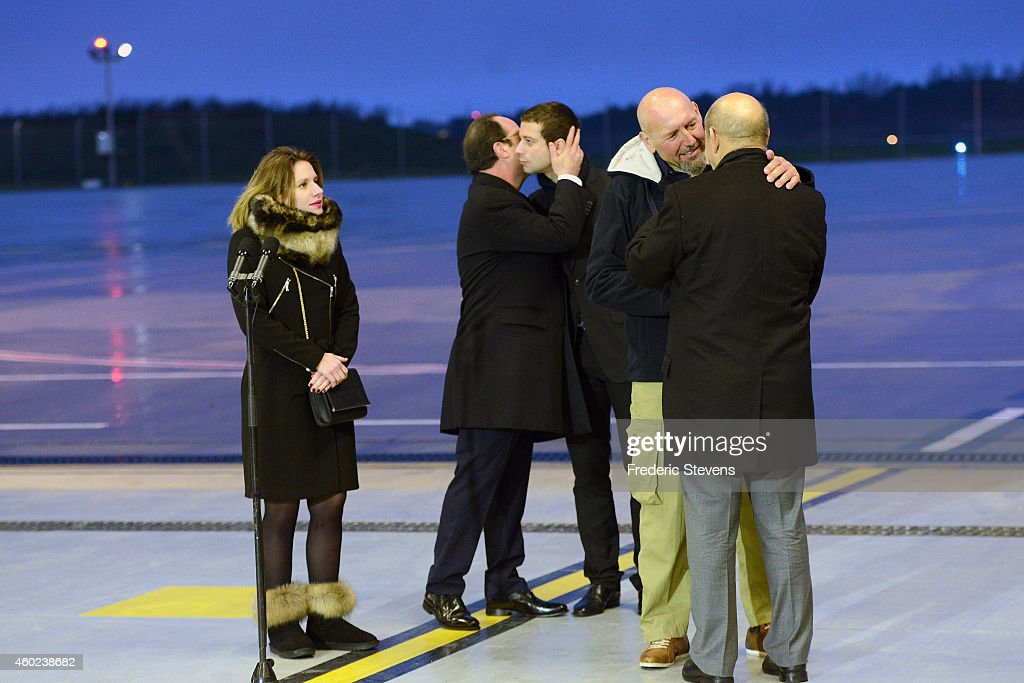 Former hostage, Serge Lazarevic is welcomed by French Defence Minister Jean-Yves Le Drian (R) as French President Francois Hollande embraces Clement Verdon, son of French executed hostage Philippe Verdon while Lazarevic 's daughter Diane looks on after landing at the Villacoublay military base near Paris on December 10, 2014 in Velizy-Villacoublay, France. Mr Lazarevic, the last French hostage to be held by Islamist militants returns to France having been freed after three years, Lazarevic was snatched in Mali back in November 2011 along with fellow Frenchman Philippe Verdon. President Hollande has stated there are no more French hostages anywhere in the world.