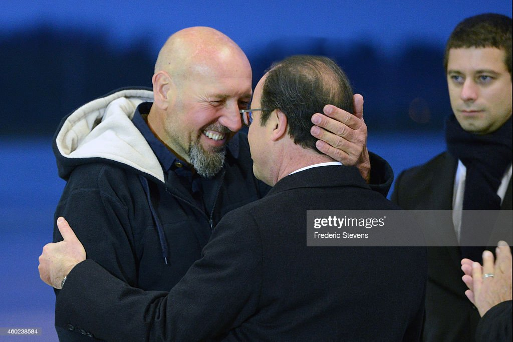 Former hostage, Serge Lazarevic is welcomed by French President Francois Hollande as Clement Verdon (R), son of French executed hostage Philippe Verdon looks on after landing at the Villacoublay military base near Paris on December 10, 2014 in Velizy-Villacoublay, France. Mr Lazarevic, the last French hostage to be held by Islamist militants returns to France having been freed after three years, Lazarevic was snatched in Mali back in November 2011 along with fellow Frenchman Philippe Verdon. President Hollande has stated there are no more French hostages anywhere in the world.