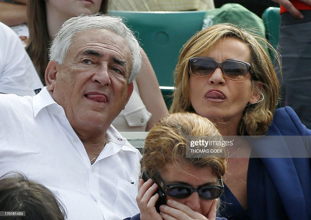 Former IMF chief Dominique Strauss-Kahn (L) and his partner, Media Marketing Executive Myriam L'Aouffir attend the women's French tennis Open final match at the Roland Garros stadium in Paris on June 8, 2013.