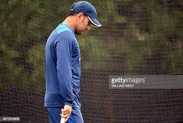 Former Indian captain MS Dhoni walks past the nets during cricket training at the Sydney Cricket Ground on January 5 2015 Australia are preparing to...