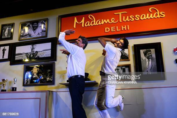 Former Indian cricket team captain Kapil Dev poses as he unveils his wax figure for the soon to open Madame Tussauds museum in New Delhi on May 11...