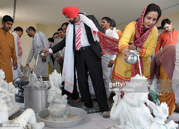 Former Indian cricketer and politician Navjot Singh Sidhu along with his wife and Member of Legislative Assembly Navjot Kaur Sidhu pour milk over...