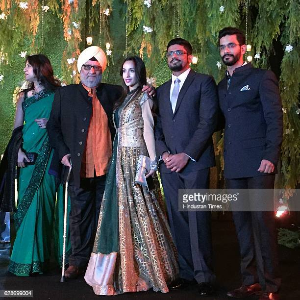 Former Indian cricketer Bishan Singh Bedi with his son and actor Angad Bedi and actor Nora Fatehi during the wedding reception of Indian Cricketer...