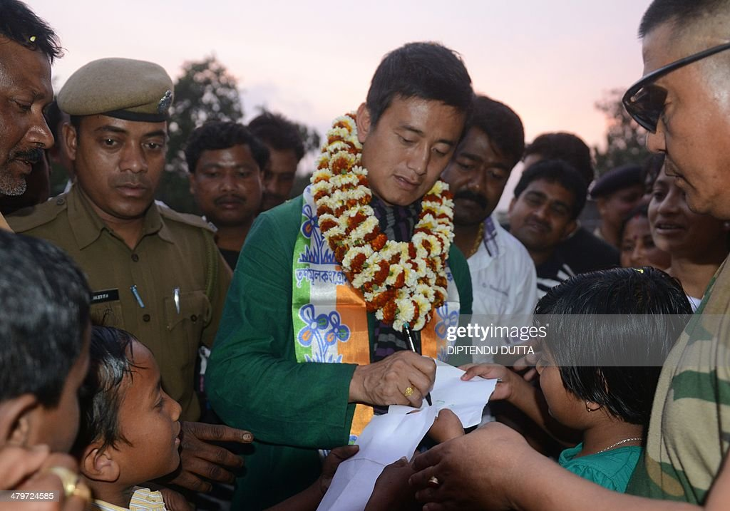 Former Indian football team captain and Trinamool Congress candidate for the Darjeeling constituency, Baichung Bhutia (C), signs autographs for children at a political rally at Batasi village some 30 kms from Siliguri on March 20, 2014. India, the world's biggest democracy, announced the start of national elections on April 7 that are expected to bring Hindu nationalist Narendra Modi to power on a platform of economic revival. AFP PHOTO /Diptendu DUTTA