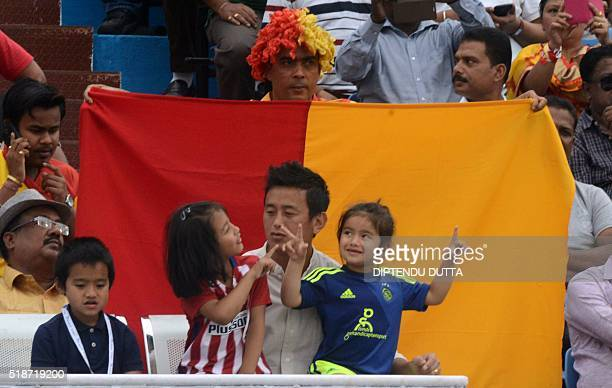 Former Indian football team captain and Trinamool Congress candidate for Darjeeling constituency Baichung Bhutiasits with his children as they watch...
