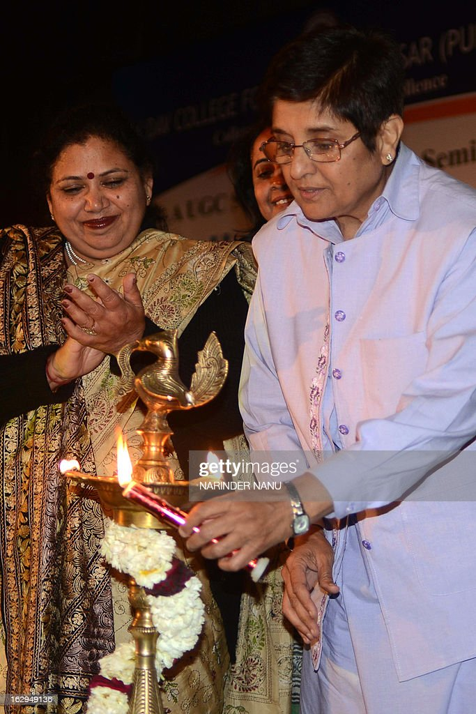 Former Indian police officer Kiran Bedi (R) lights an oil lamp before delivering a speech during a national seminar on human rights at a women's college in Amritsar on March 2, 2013. Bedi called for a holistic approach to deal with crimes against women.