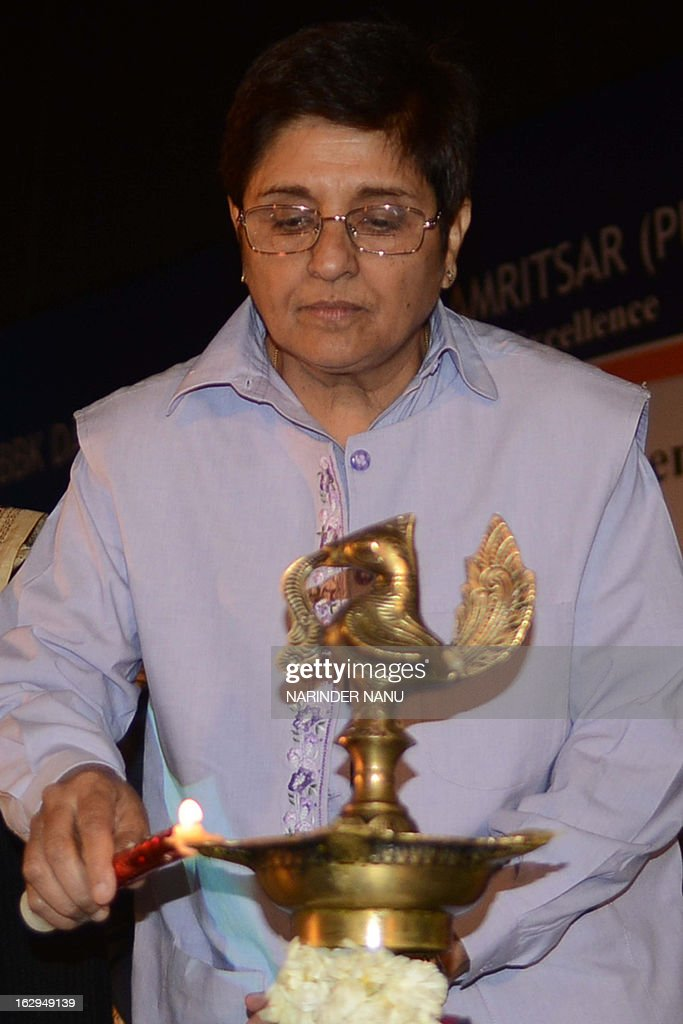 Former Indian police officer Kiran Bedi lights an oil lamp before delivering a speech during a national seminar on human rights at a women's college in Amritsar on March 2, 2013. Bedi called for a holistic approach to deal with crimes against women.