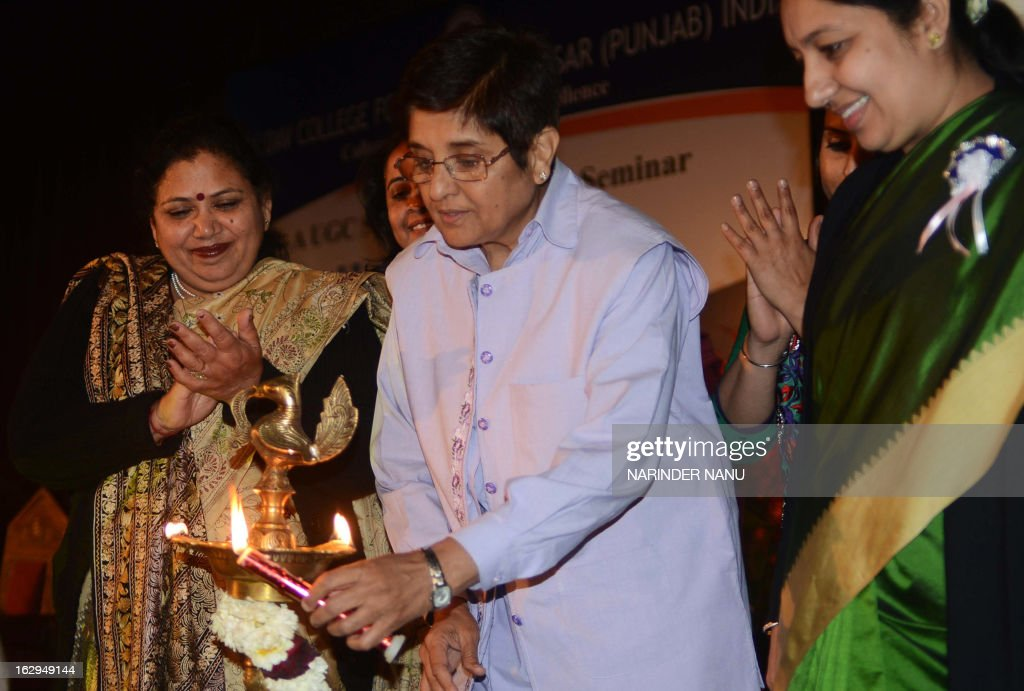 Former Indian police officer Kiran Bedi (C) lights an oil lamp before delivering a speech during a national seminar on human rights at a women's college in Amritsar on March 2, 2013. Bedi called for a holistic approach to deal with crimes against women.