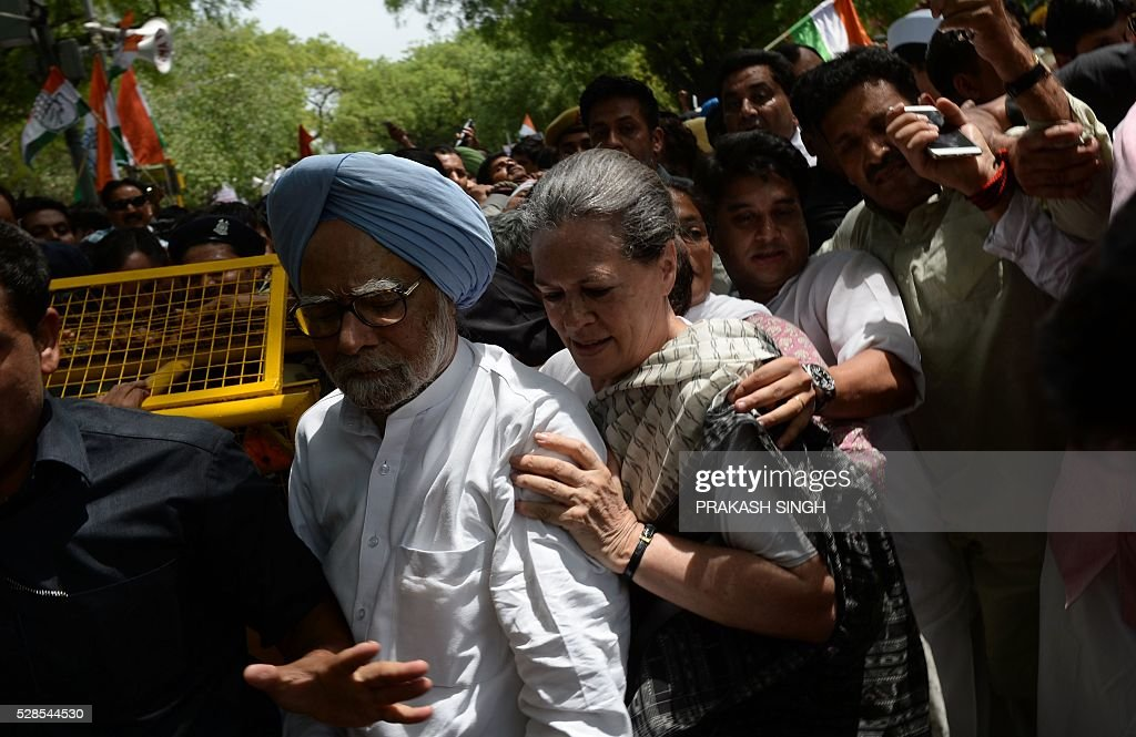Former Indian prime minister Manmohan Singh (L) and Congress Party President Sonia Gandhi (C) take part in the 'March for Democracy' protest against the National Democratic Alliance (NDA) government led by the Bharatiya Janata Part's (BJP) Narendra Modi in New Delhi on May 6, 2016. Former Indian prime minister Manmohan Singh, Congress Party President Sonia Gandhi and party Vice-president Rahul Gandhi were briefly arrested at a police station and later released during a 'Save Democracy' protest march against the ruling Bharatiya Janata Party (BJP). / AFP / PRAKASH