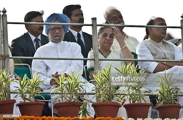 Former Indian prime minister Manmohan Singh listens to a speech by India's new Prime Minister Narendra Modi at the Red Fort to mark the country's...