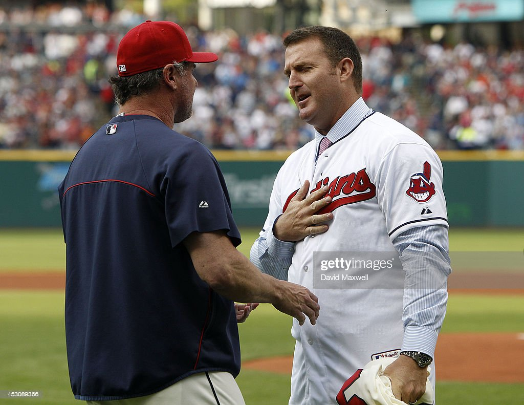 Former Indians great Jim Thome #25 thanks Indians player Jason Giambi #25 after Giambi relinquished his number 25 so that Thome, who announced his retirement today, could retire as an Indian with his playing number 25 before the game between the Cleveland Indians and the Texas Rangers on August 2, 2014 at Progressive Field in Cleveland, Ohio.
