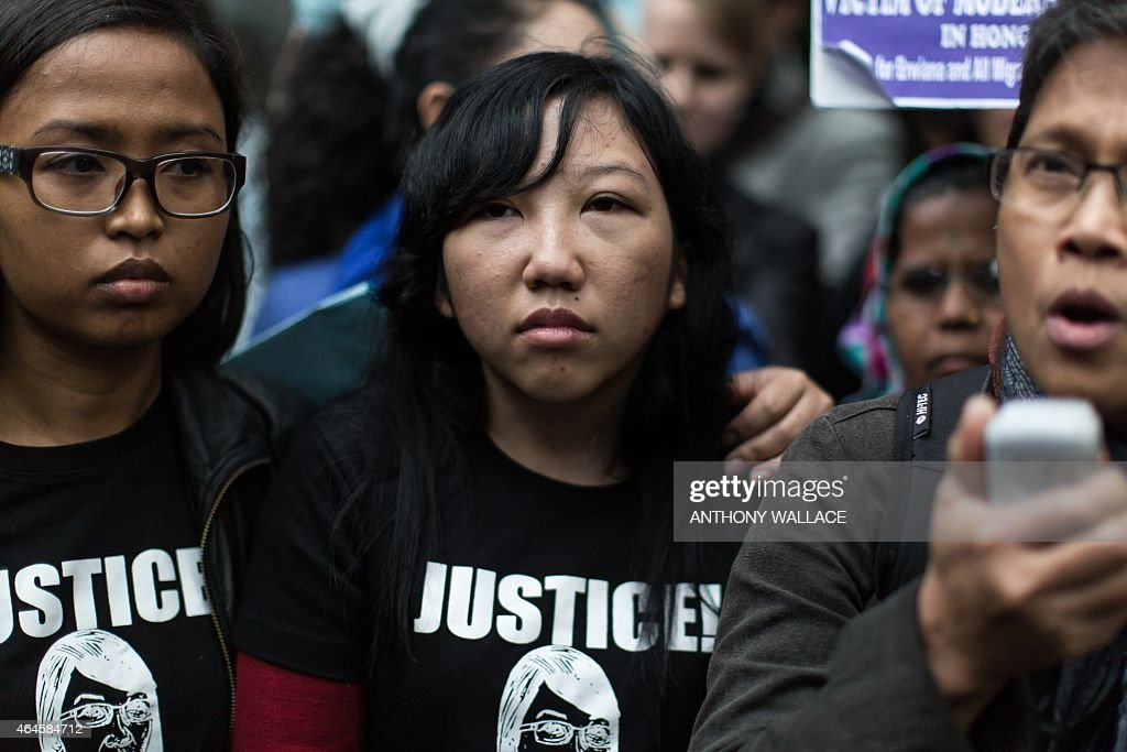 Former Indonesian domestic helper <a gi-track='captionPersonalityLinkClicked' href=/galleries/search?phrase=Erwiana+Sulistyaningsih&family=editorial&specificpeople=12341887 ng-click='$event.stopPropagation()'>Erwiana Sulistyaningsih</a> (C) looks on as a supporter (R) speaks to the press in front of the District Court following the sentencing of her former employer Law Wan-tung in Hong Kong on February 27, 2015. Law was jailed for six years on February 27 for beating and starving Sulistyaningsih and keeping her prisoner, as the judge called for action over laws which leave domestic workers exposed to abuse.