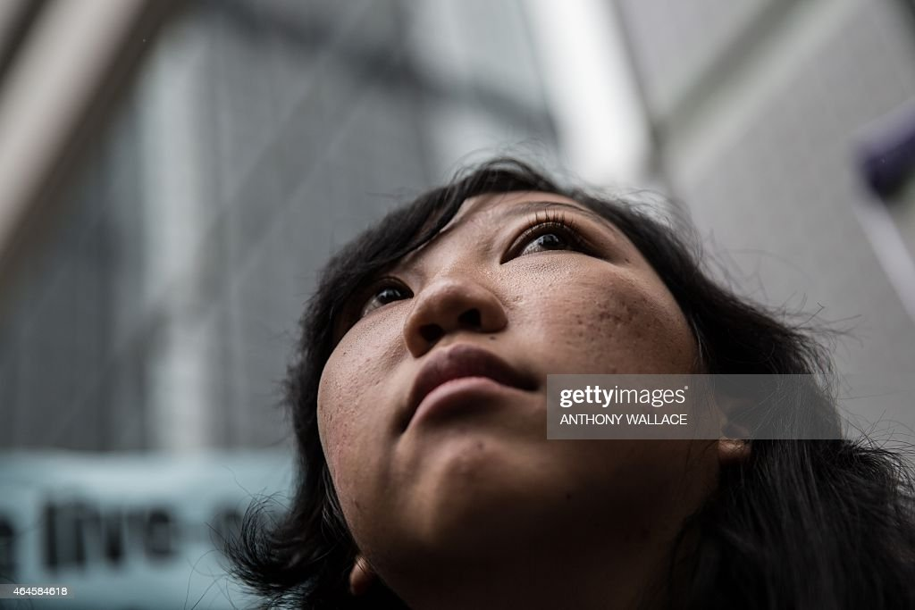 Former Indonesian domestic helper <a gi-track='captionPersonalityLinkClicked' href=/galleries/search?phrase=Erwiana+Sulistyaningsih&family=editorial&specificpeople=12341887 ng-click='$event.stopPropagation()'>Erwiana Sulistyaningsih</a> looks on in front of the District Court following the sentencing of her former employer Law Wan-tung in Hong Kong on February 27, 2015. Law was jailed for six years on February 27 for beating and starving Sulistyaningsih and keeping her prisoner, as the judge called for action over laws which leave domestic workers exposed to abuse.