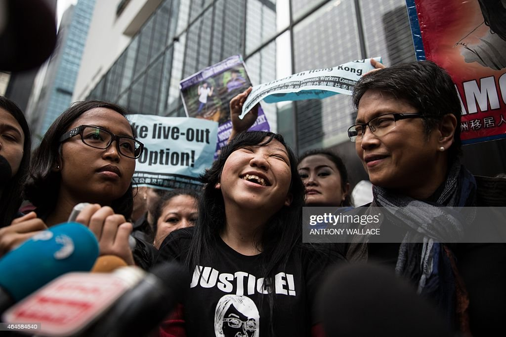 Former Indonesian domestic helper <a gi-track='captionPersonalityLinkClicked' href=/galleries/search?phrase=Erwiana+Sulistyaningsih&family=editorial&specificpeople=12341887 ng-click='$event.stopPropagation()'>Erwiana Sulistyaningsih</a> (C) reacts as she speaks to the press in front of the District Court following the sentencing of her former employer Law Wan-tung in Hong Kong on February 27, 2015. Law was jailed for six years on February 27 for beating and starving Sulistyaningsih and keeping her prisoner, as the judge called for action over laws which leave domestic workers exposed to abuse.