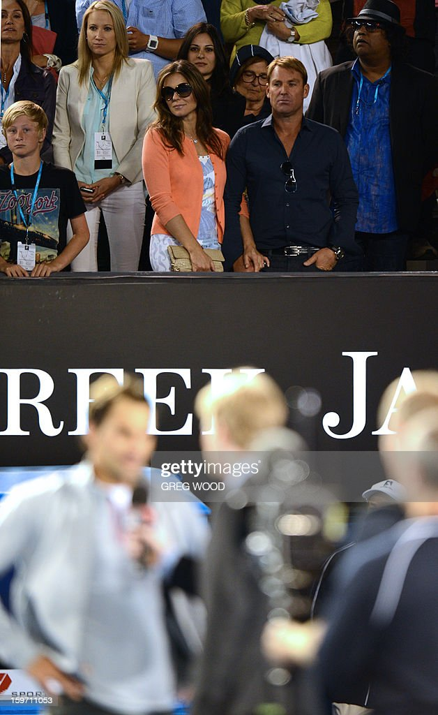 Former international cricketer Shane Warne (R) and British actress Elizabeth Hurley (C) look on as Switzerland's Roger Federer gives an oncourt interview after his men's singles match against Australia's Bernard Tomic on the sixth day of the Australian Open tennis tournament in Melbourne on January 19, 2013. AFP PHOTO/GREG WOOD IMAGE STRICTLY RESTRICTED TO EDITORIAL USE - STRICTLY NO COMMERCIAL USE