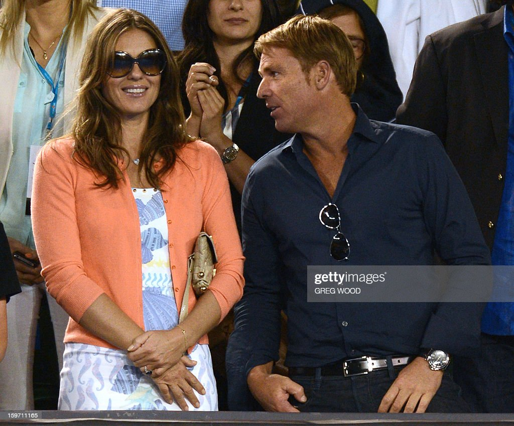 Former international cricketer Shane Warne (R) and British actress Elizabeth Hurley look on as Switzerland's Roger Federer gives an oncourt interview after his men's singles match against Australia's Bernard Tomic on the sixth day of the Australian Open tennis tournament in Melbourne on January 19, 2013.