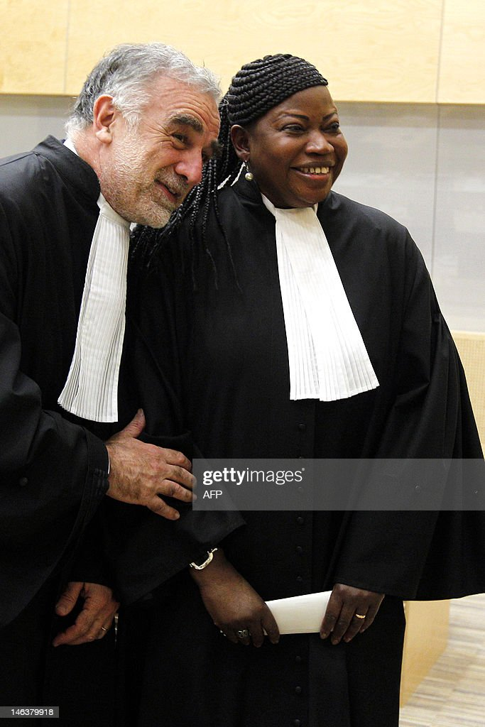 Former International Criminal Court's chief prosecutor Luis Moreno-Ocampo (L) shares a laugh with ICC's new chief <a gi-track='captionPersonalityLinkClicked' href=/galleries/search?phrase=Fatou+Bensouda&family=editorial&specificpeople=802492 ng-click='$event.stopPropagation()'>Fatou Bensouda</a> (R) after her swearing-in ceremony as the International Criminal Court's new chief prosecutor in The Hague, on June 15, 2012. The 51-year-old Bensouda is the first woman and the first African to head the team of prosecutors at the tribunal, which is currently investigating 15 cases in seven countries, all of them African. Taking the oath before ICC judges and a public gallery packed with foreign diplomats and dignitaries, Bensouda vowed to continue to pursue those wanted for crimes of genocide, war crimes and crimes against humanity. AFP PHOTO/POOL/BAS CZERWINSKI netherlands out