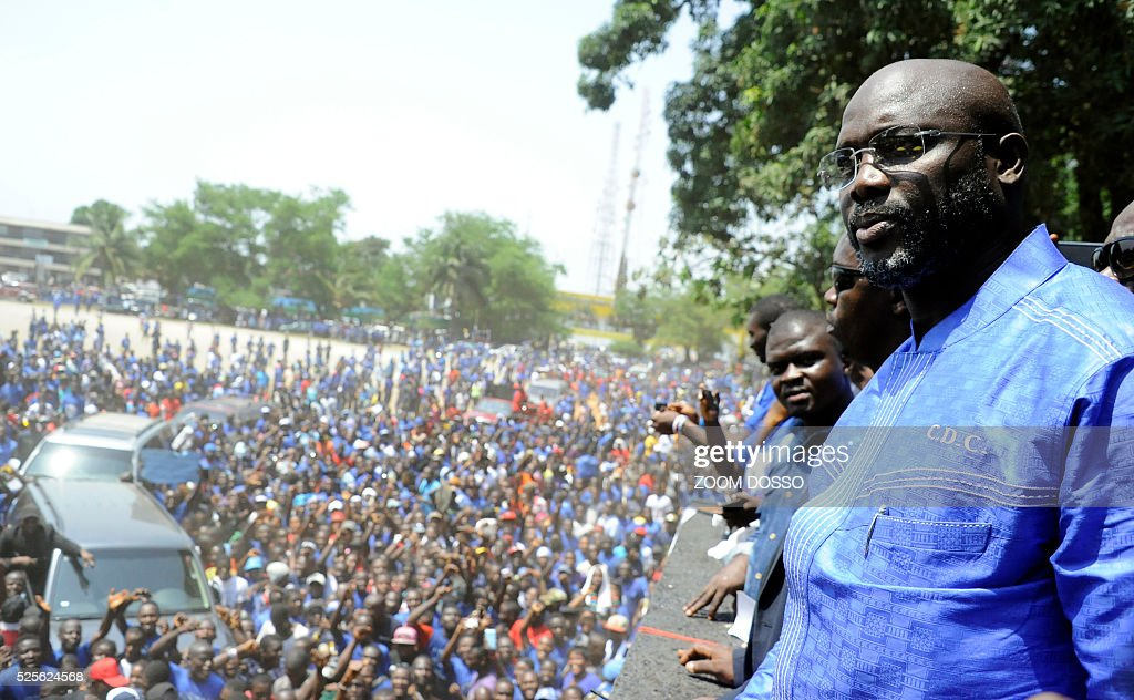 Former international football star George Weah looks at his supporters on April 28, 2016 at the his party's headquarters in Monrovia. Former international football star George Weah today said he would be a candidate in next year's presidential elections in Liberia -- his second bid for the post. As Sirleaf is ineligible to stand for a third term under Liberia's constitution, Weah is expected to face her vice president, Joseph Boakai, 71. / AFP / ZOOM