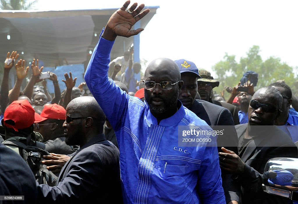 Former international football star George Weah waves to suppoters on April 28, 2016 at the his party's headquarters in Monrovia. Former international football star George Weah today said he would be a candidate in next year's presidential elections in Liberia -- his second bid for the post. As Sirleaf is ineligible to stand for a third term under Liberia's constitution, Weah is expected to face her vice president, Joseph Boakai, 71. / AFP / ZOOM