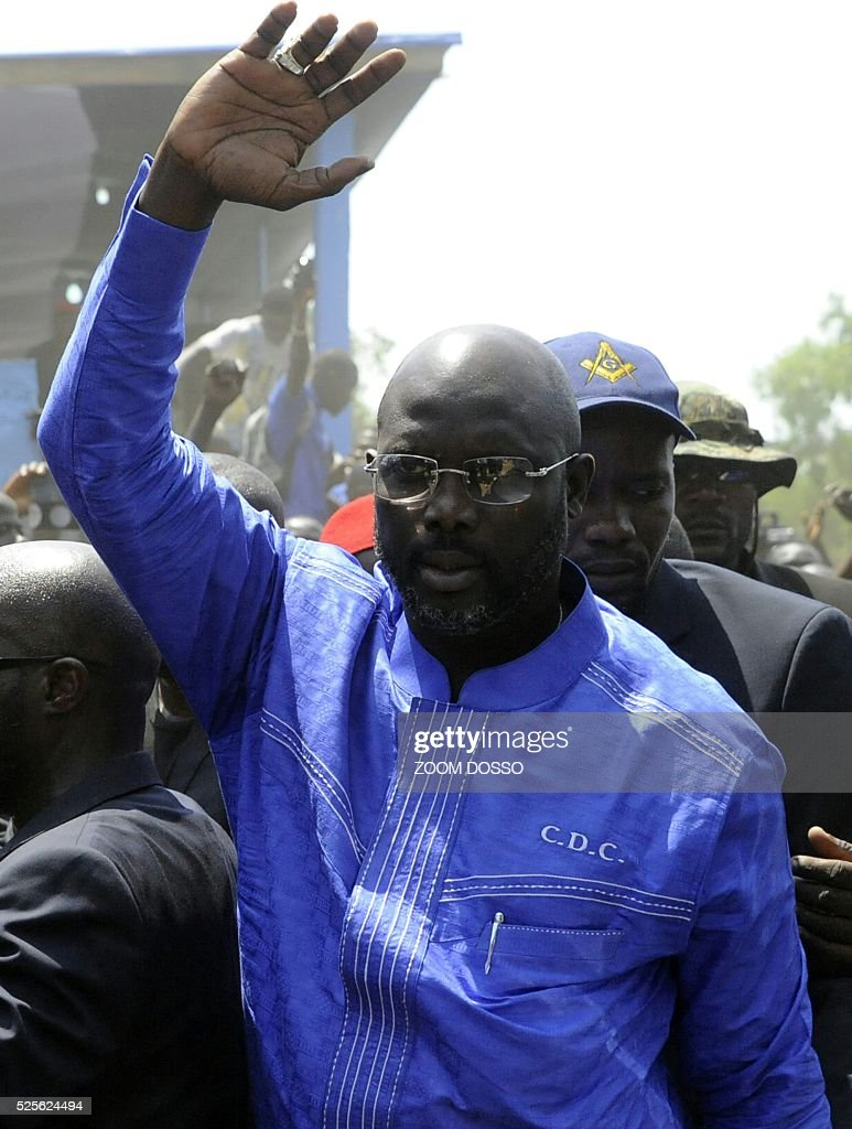 Former international football star George Weah waves to supporters on April 28, 2016 at the his party's headquarters in Monrovia. Former international football star George Weah today said he would be a candidate in next year's presidential elections in Liberia -- his second bid for the post. As Sirleaf is ineligible to stand for a third term under Liberia's constitution, Weah is expected to face her vice president, Joseph Boakai, 71. / AFP / ZOOM
