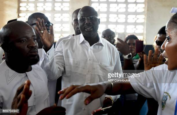 Former international Liberian football icon turned politician and presidential election candidate George Weah prepares to cast his vote at a polling...