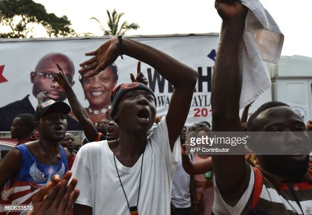 TOPSHOT Former international Liberian football icon turned politician and presidential election candidate George Weah supporters celebrates on...