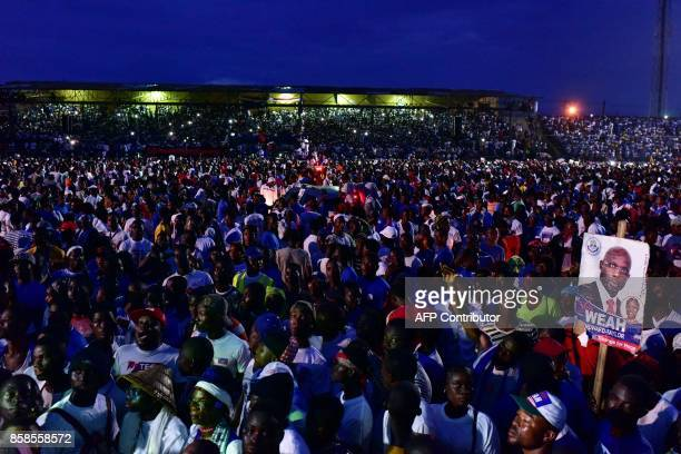Former international Liberian football star turned politician George Weah supporters attend a presidential campaign rally in Monrovia on October 6...