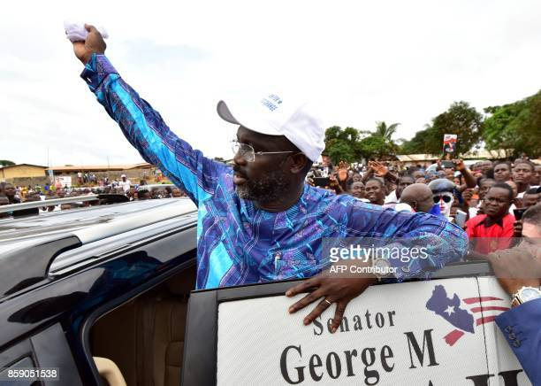 Former international Liberian football star turned politician George Weah waves to supporters during a campaign rally in Monrovia on October 8 three...