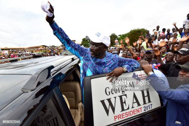 Former international Liberian football star turned politician George Weah greets his supporters during a campaign rally in Monrovia on October 8...