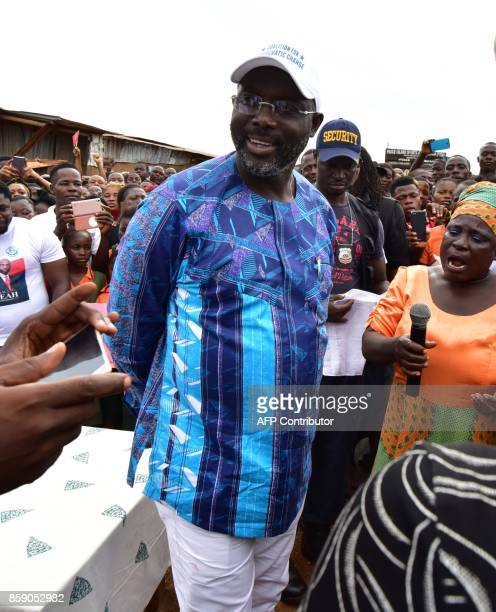 Former international Liberian football star turned politician George Weah greets supporters during a campaign rally in Monrovia on October 8 three...