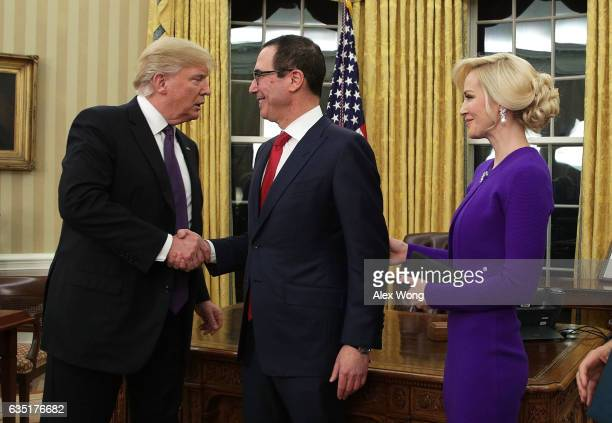 Former investment banker for Goldman Sachs Steven Mnuchin shakes hands with President Donald Trump as fiancee Louise Linton looks on during a...