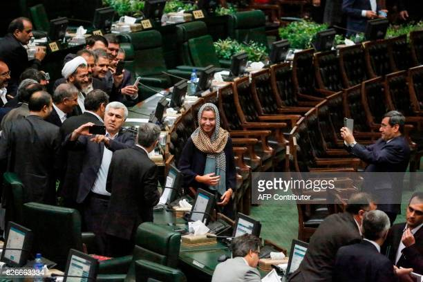 Former Iranian foreign ministry spokesman Hassan Ghashghavi uses a cell phone to take a picture of EU foreign policy chief Federica Mogherini...