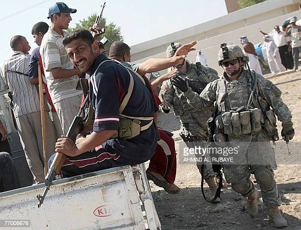 Former Iraqi insurgents members of the Sunni Anbar Awakening greet US army soldiers their former enemies while guarding a meeting between Sunni and...