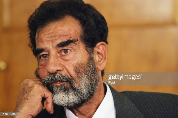 Former Iraqi President Saddam Hussein listens as a list of charges that he and 11 other high level defendents will face is read in an Iraqi courtroom...