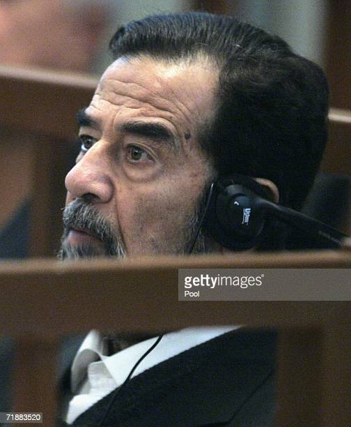 Former Iraqi President Saddam Hussein listens to a defence testimony during the fourth day of his trial on genocide charges in the fortified Green...