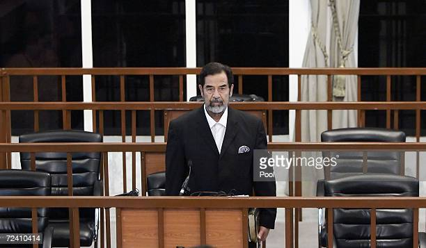 Former Iraqi President Saddam Hussein stands as he receives his guilty verdict during his trial in the fortified 'green zone' on November 5 2006 in...