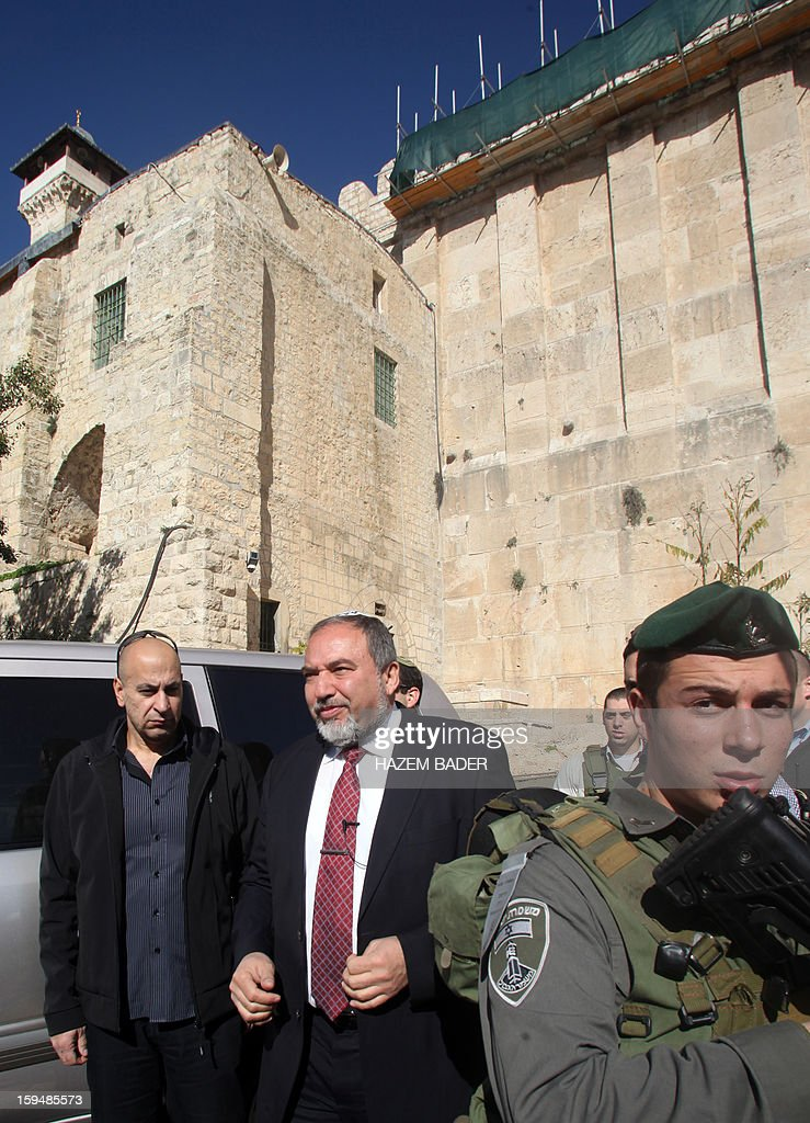 Former Israel Minister for Foreign Affairs Avigdor Liberman is surrounded by security at the Ibrahimi Mosque, a holy site to both Muslims and Jews who refer to it as the Tombs of the Patriarchs, in the old quarter of the southern West Bank city of Hebron on January 14, 2013, during his campaign visit to the divided city to meet Israeli settlers in the Kiryat Arbaa settlement and in the settlers zones in the center of the city. Israel goes to the polls on January 22. AFP PHOTO / HAZEM BADER
