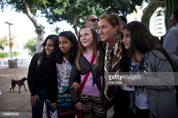 Former Israeli foreign minister Tzipi Livni the leader of the new party The Movement poses with people while campaigning on January 18 2013 in Tel...