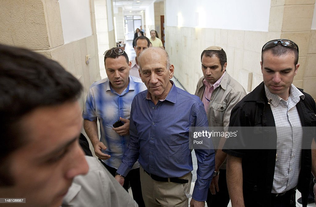 Former Israeli Prime Minister <a gi-track='captionPersonalityLinkClicked' href=/galleries/search?phrase=Ehud+Olmert&family=editorial&specificpeople=178946 ng-click='$event.stopPropagation()'>Ehud Olmert</a> (C) arrives at the District Court for the hearing of the verdict in his trial on corruption charges concerned with the Holyland real estate scandal that forced his resignation from power, on July 10, 2012 in Jerusalem, Israel. Olmert was acquitted on two major charges of corruption relating to the Rishon Tours and Talansky affairs, and found guilty on one charge of breach of trust in the Investment Center affair. Bureau chief to the former Prime Minister, Shula Zaken was convicted on two counts of fraud and breach of trust in the Rishon Tours affair.