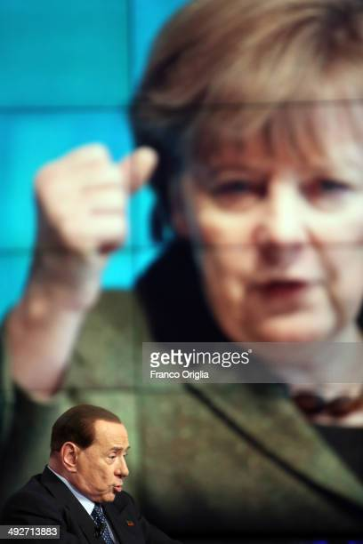Former Italian Prime Minister Silvio Berlusconi attends the 'Porta A Porta' TV show at the RAI TV studios while a portrait of German Chancellor...