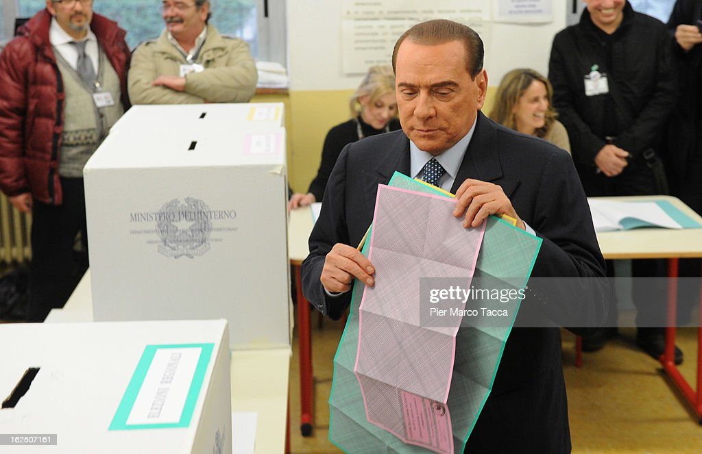 Former Italian Prime Minister Silvio Berlusconi holds papers as he casts his vote in a polling station on February 24, 2013 in Milan, Italy. Italians are heading to the polls today to vote in the elections, as the country remains in the grip of economic problems. Pier Luigi Bersani's centre-left alliance is believed to be a few points ahead of the centre-right bloc led by ex-Prime Minister Silvio Berlusconi.