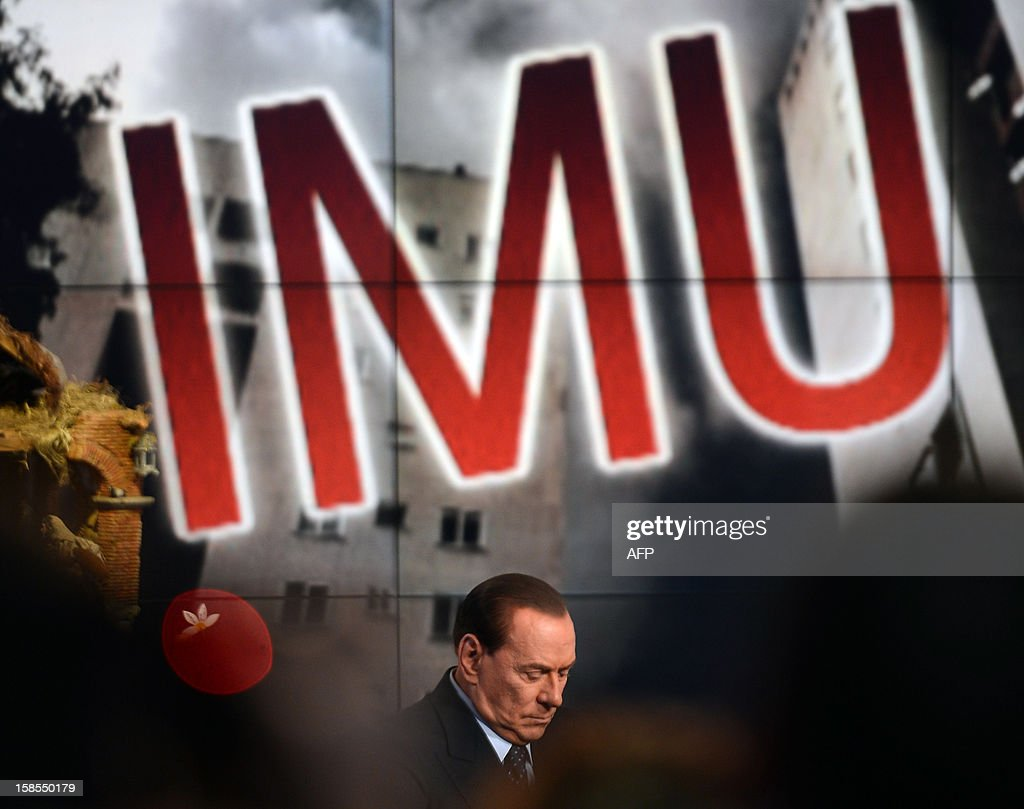 Former Italian Prime Minister Silvio Berlusconi reacts on the set of RAI 1 television programme 'Porta a Porta' on December 18, 2012 in Rome. Silvio Berlusconi the day before said a German-dominated Europe had imposed austerity on Italy as the three-time prime minister prepares for his sixth election campaign in two decades in politics. Flower reads 'No come back'. AFP PHOTO / FILIPPO MONTEFORTE