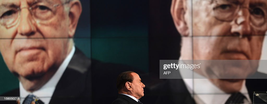 Former Italian Prime Minister Silvio Berlusconi reacts on the set of RAI 1 television programme 'Porta a Porta' with a portrait of current Prime Minister Mario Monti in the background on December 18, 2012 in Rome. Silvio Berlusconi the day before said a German-dominated Europe had imposed austerity on Italy as the three-time prime minister prepares for his sixth election campaign in two decades in politics. Flower reads 'No come back'. AFP PHOTO / FILIPPO MONTEFORTE