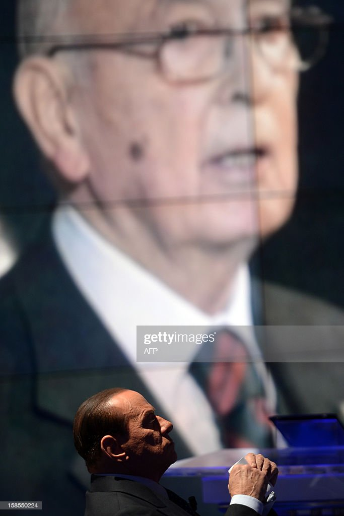 Former Italian Prime Minister Silvio Berlusconi reacts on the set of RAI 1 television programme 'Porta a Porta' with a portrait of President Giorgio Napolitano in the background on December 18, 2012 in Rome. Silvio Berlusconi the day before said a German-dominated Europe had imposed austerity on Italy as the three-time prime minister prepares for his sixth election campaign in two decades in politics. Flower reads 'No come back'. AFP PHOTO / FILIPPO MONTEFORTE