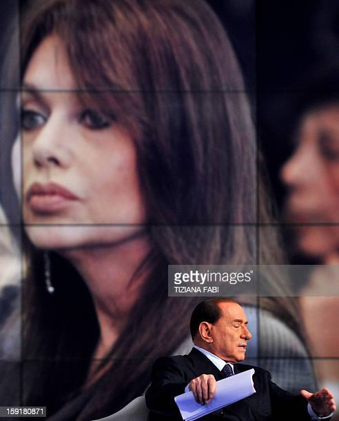 Former Italian Prime Minister Silvio Berlusconi sits on the set of the RAI 1 television programme 'Porta a Porta' while a portrait of his second wife...