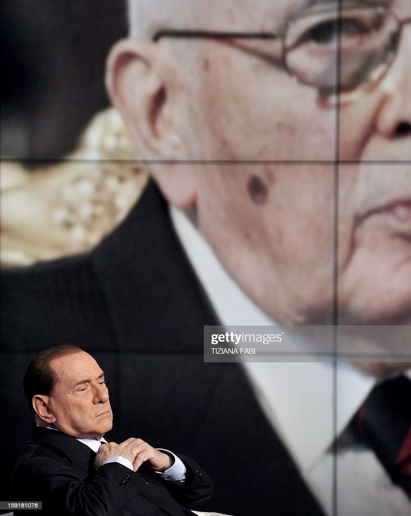 Former Italian Prime Minister Silvio Berlusconi sits on the set of the RAI 1 television programme 'Porta a Porta' while a portrait of Italian President Giorgio Napolitano is displayed in the background on January 9, 2013 in Rome. Italy's Silvio Berlusconi revived his historic alliance with the far-right Northern League on Monday and stepped back from his leadership bid in a deal to shore up support ahead of February elections.